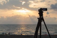 Digital Video Camera shooting the Beach at Sunset on sea.  twilight sky and cloud landscape Royalty Free Stock Photography