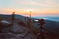 Digital video camera on tripod filming sunrise at mountains. Stock Images