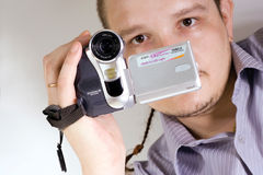 The digital videocamera. The man holds an amateur digital videocamera Royalty Free Stock Photography