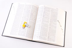 Digital vs Paper (Open Dictionary Top View). Yellow USB memory stick on an open dicitionary, isolated on white background Stock Image