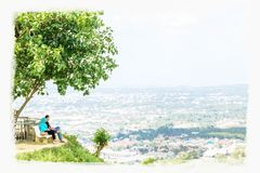 Hatyai,Thailand top view. Digital water painting of a couple sitting on chair at the hill looking to the landscape view royalty free stock photos
