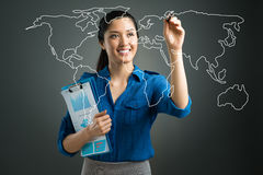 Digital world map. Isolated image of a young businesswoman pointing with a pen at the world map on digital interface Stock Photos