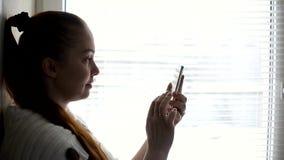 Digitala teknologier och kommunikationer, medel?lders kvinna som bl?ddrar internetplatser p? smartphonesk?rmen som f?rbi sitter lager videofilmer