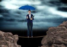 Digitalbild der Geschäftsfrau stehend auf Seil unter den Felsen, die blauen Regenschirm gegen bewölkte SK halten Lizenzfreies Stockfoto
