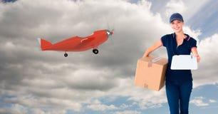 Digitalbild des weiblichen liefernden bereitstehenden Flugzeuges des Paketes auf Himmel Stockbilder