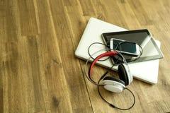Digitale apparaten en Hoofdtelefoons op een houten Desktop royalty-vrije stock afbeeldingen