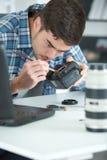 Digitale camera van de fotograaf de schoonmakende lens Stock Foto's
