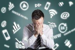 Digitale media symbolen die rond een uitgeputte mens wervelen stock foto