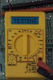 Digitale multimeter multitester op een kringsraad met woord het testen stock afbeelding