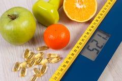 Digitale schaal met meetlint, domoren, tabletten, vruchten, vermageringsdieetconcept Stock Fotografie