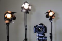Digitale SLR-camera en drie schijnwerpers met Fresnel lenzen Hand verwisselbare lens voor film Royalty-vrije Stock Foto