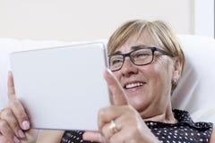 Digitale tablet die door hogere vrouw gebruiken Stock Foto's