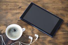 Digitale tablet en een kop van koffie stock afbeeldingen