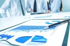 Digitale tablet en financiële grafieken op de Desktop op de achtergrond van het commerciële team stock afbeeldingen