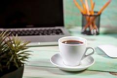 Digitale tablet en kop van koffie op oud houten bureau Eenvoudige werkruimte of koffiepauze in ochtend Royalty-vrije Stock Afbeelding