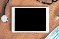 Digitale tablet op een medisch bureau met stethoscoop, spuit en hygiënisch masker Lege ruimte of spatie voor bericht of uw tekst stock afbeeldingen