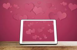 Digitale tablet op houten bureau met drijvende harten op roze achtergrond Stock Afbeeldingen