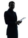 Digitale Tablette des Geschäftsmannes, die Porträtschattenbild aufwirft Lizenzfreie Stockbilder