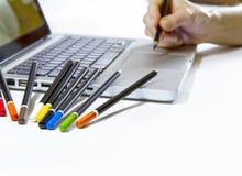 Digitale of traditionele grafische kunsten? De hand van een vrouw schijnt om op het aanrakingsstootkussen van een laptop computer royalty-vrije stock fotografie
