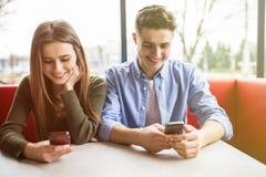 Digitale verslaving Aantrekkelijk aardig paar die terwijl het houden van telefoons en het staren bij het dateren royalty-vrije stock fotografie