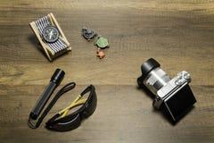 Digitalkamera mit Blitzlicht und Sonnenbrille auf hölzernem Hintergrund Lizenzfreie Stockfotos