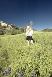 Digitally altered, high contrast image of blond girl walking through green fields filled with lupine flowers in the spring in Ojai Royalty Free Stock Images