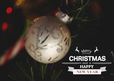 Digitally composite image of merry christmas and happy new year message against christmas bauble Stock Photos