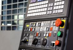 Emergency stop button depth of field, focus blur in CNC machine control panel with machining machine and late process. Digitally controlled modern cnc lathe in a Royalty Free Stock Photography