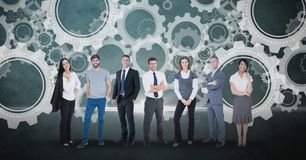 Digitally generated image of business people standing against gears in background. Digital composite of Digitally generated image of business people standing Stock Image