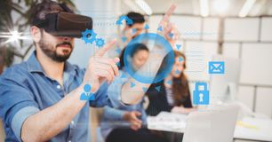 Digitally generated image of businessman touching icons while using VR glasses with colleagues in ba. Digital composite of Digitally generated image of royalty free stock photo