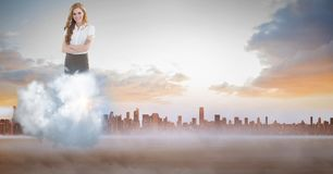 Digitally generated image of businesswoman on cloud against city. Digital composite of Digitally generated image of businesswoman on cloud against city Stock Photo