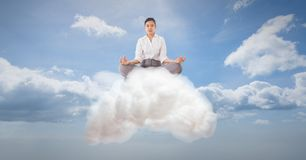 Digitally generated image of businesswoman meditating on cloud in sky Stock Photos