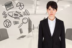 Digitally generated image of businesswoman standing by various icons in office Royalty Free Stock Photography