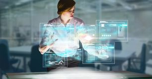 Digitally generated image of businesswoman touching futuristic screen in office. Digital composite of Digitally generated image of businesswoman touching Stock Photos