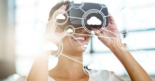 Digitally generated image of cloud computing icons with woman using VR glasses in office Stock Images