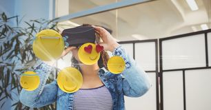 Digitally generated image of emojis flying against woman using VR glasses at home Royalty Free Stock Photography