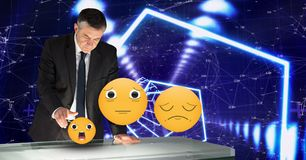 Digitally generated image of emojis flying by businessman touching futuristic desk Stock Photos