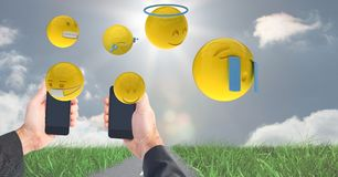 Digitally generated image of emojis flying over hands holding smart phone at field against sky. Digital composite of Digitally generated image of emojis flying Stock Image