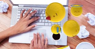 Digitally generated image of emojis flying over hands using laptop at table Stock Photo