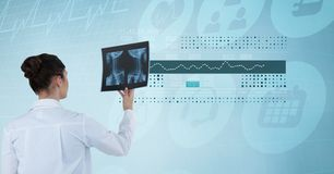 Digitally generated image of female doctor holding x-ray against futuristic screen. Digital composite of Digitally generated image of female doctor holding x-ray Royalty Free Stock Photos