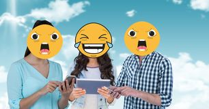 Digitally generated image of friends faces covered with emoji using digital tablet and smart phone a Royalty Free Stock Photo