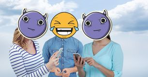 Digitally generated image of friends faces covered with emoji using smart phones against sky Stock Photo