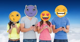 Digitally generated image of friends faces covered with emoji using smart phones against sky Royalty Free Stock Photography