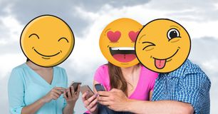 Digitally generated image of friends faces covered with emoji using smart phones against sky. Digital composite of Digitally generated image of friends faces Royalty Free Stock Images
