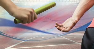 Digitally generated image of hands passing the baton. In stadium stock photo