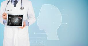 Digitally generated image of male doctor showing digital tablet with human face graphics in backgrou. Digital composite of Digitally generated image of male Stock Images