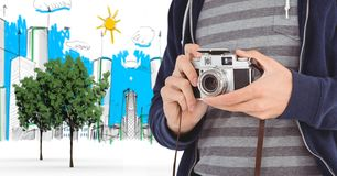 Digitally generated image of male tourist holding camera with buildings drawn in background. Digital composite of Digitally generated image of male tourist Stock Images