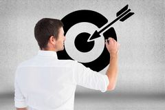 Digitally generated image of man drawing target icon against gray background. Digital composite of Digitally generated image of man drawing target icon against Royalty Free Stock Photography