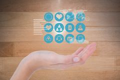 Digitally generated image of various icons over hand against wooden wall stock image