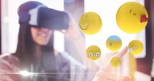 Digitally generated image of woman touching flying emojis while using VR glasses. Digital composite of Digitally generated image of woman touching flying emojis Stock Photos